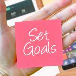 Set Goals phrase on sticky note in hand